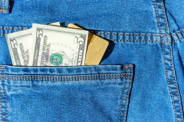 청바지 주머니 돈 개념에 달러 현금이 있는 신용 플라스틱 은행 카드