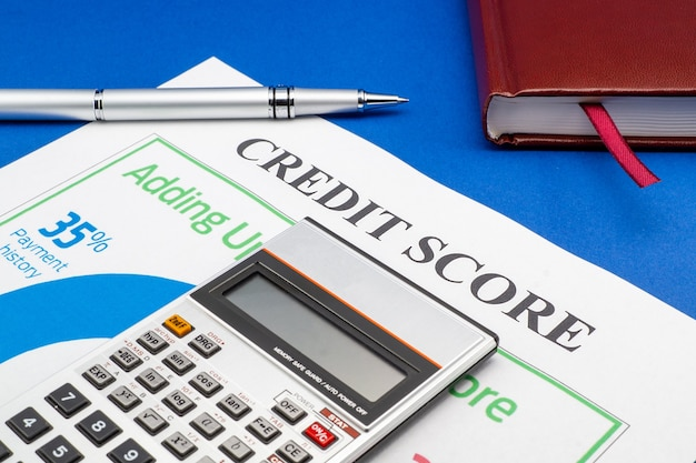 Credit score report with keyboard and notepad on a blue table.