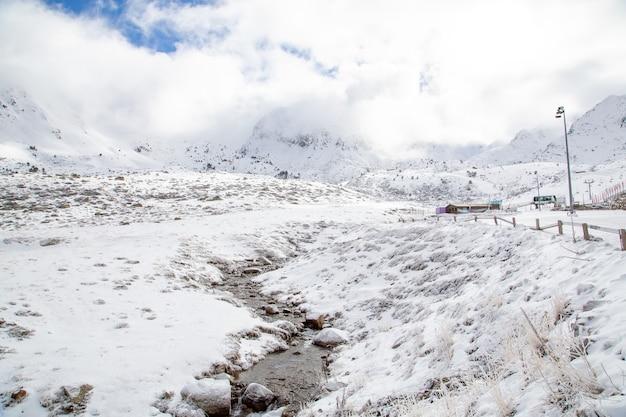 曇り空の下で雪に覆われた高山に囲まれた小川