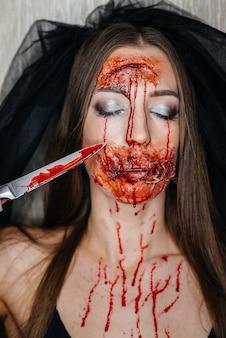 할로윈에 소름 끼치는 피 묻은 메이크업 소녀. 인공 화장과 행사.