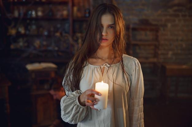 소름 끼치는 악마 여자는 촛불을 들고 악마가 튀어 나와 있습니다. 엑소시즘, 미스터리 초자연적 의식, 암흑 종교, 밤 공포, 선반 위의 물약