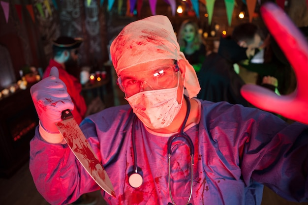Creepy doctor with his covered holing a kinfe with blood and looking into the camera at halloween party. halloween event.