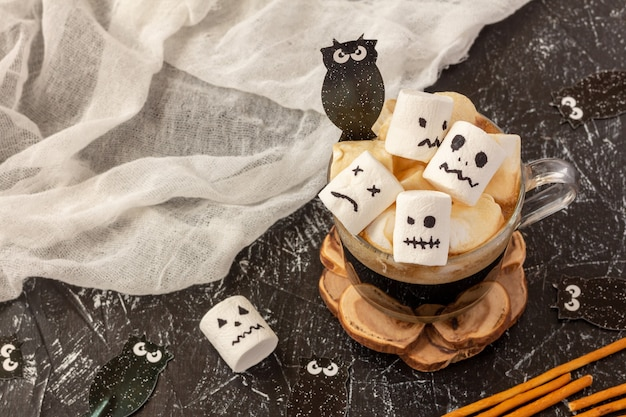 Creepy faces (monster) from marshmallows in cup of coffee for halloween