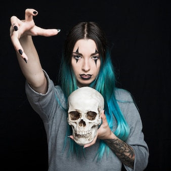 Creepy female holding human skull