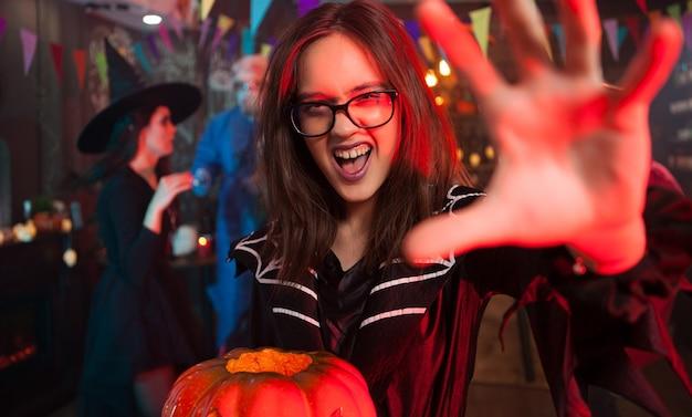 カメラに手を差し伸べるハロウィーンの衣装を着た不気味な女の子。ハロウィーンのために集まっているモンスター。美しい魔女。