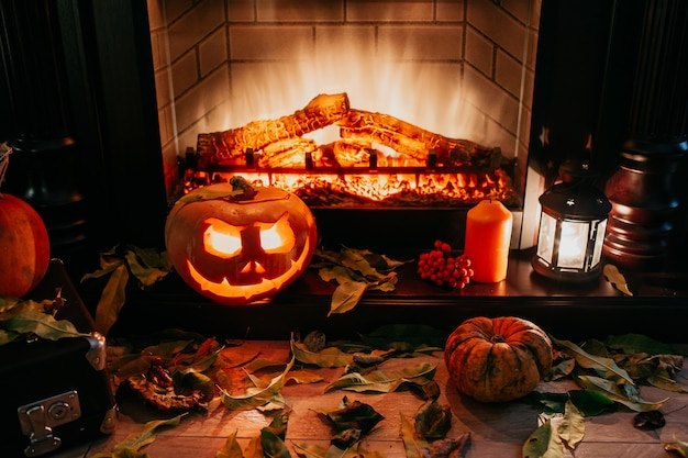 Creepy halloween pumpkin near a fireplace. fire and dry leaves on the background. jack of the lantern, copyspace. shoot in the dark.