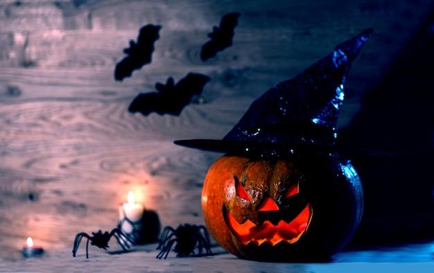 Жуткая тыква на хэллоуин в шляпе ведьмы на деревянном фоне. happy halloween concept