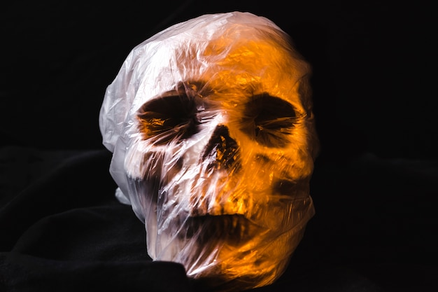 Creepy skull in plastic bag illuminated by orange light