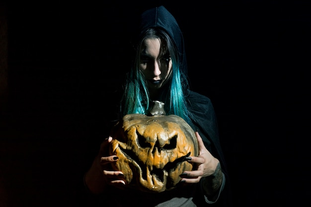 Creepy woman in hood holding pumpkin