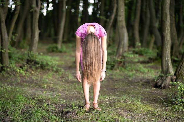 변덕스러운 어두운 숲에서 구부러진 긴 머리를 가진 소름 끼치는 여자