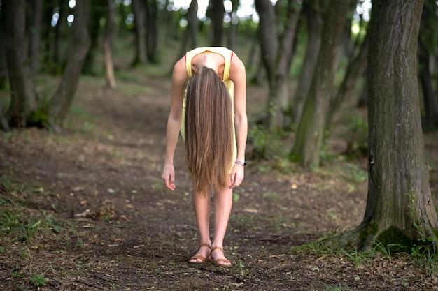 不機嫌そうな暗い森の中で腰をかがめて立っている長い髪の不気味な女性。