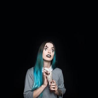 Жуткая молодая женщина, стоящая с рукой зомби