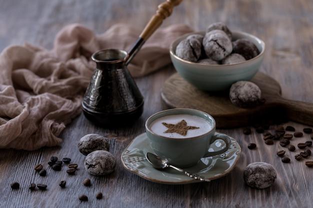 Чашка кофе crema с шоколадным печеньем, зефиром и зажженными свечами.