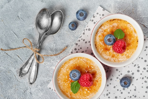 Creme brulee (cream brulee, burnt cream) bowls decorated with with raspberry, blueberry and mint