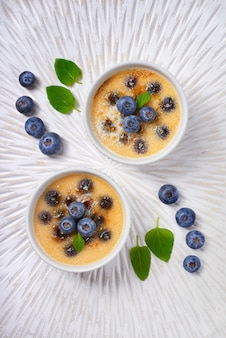 Creme brulee (cream brulee, burnt cream) with blueberry and lavender powdered with sugar on light