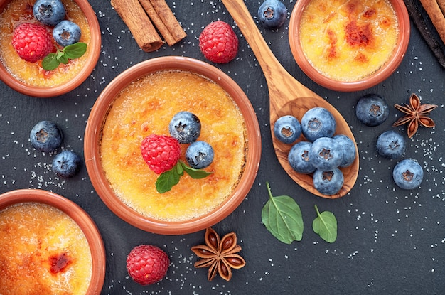 Creme brulee (cream brulee, burnt cream) with raspberry, blueberry and mint in terracota clay baking dishes