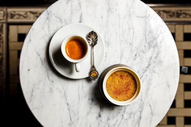 Creme brulee dessert and a cup of espresso with a beautiful old spoon on a marble table, top view