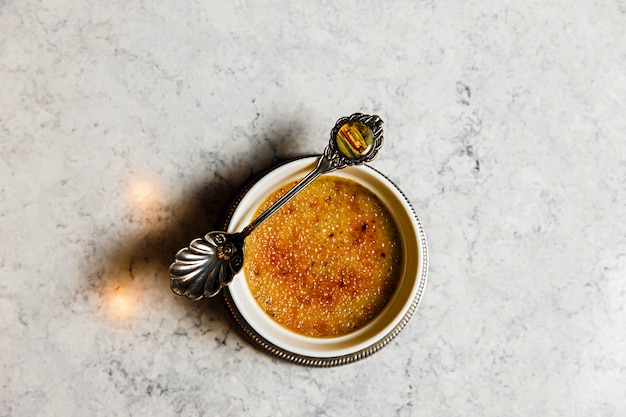 Creme brulee dessert with a beautiful old spoon on a marble table, top view