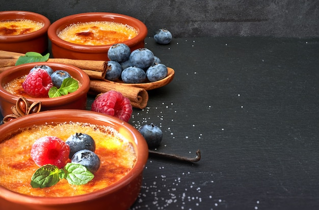 Creme brulee with berries and ingredients on dark stone, space