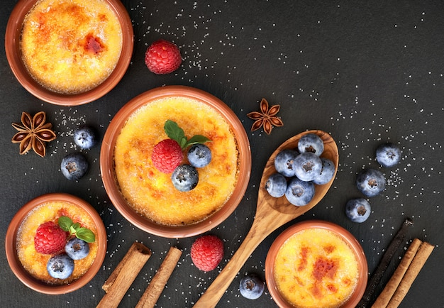 Creme brulee with berries and ingredients on dark stone, top view