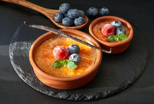 Creme brulee with raspberry, blueberry and mint leaves on dark slate stone