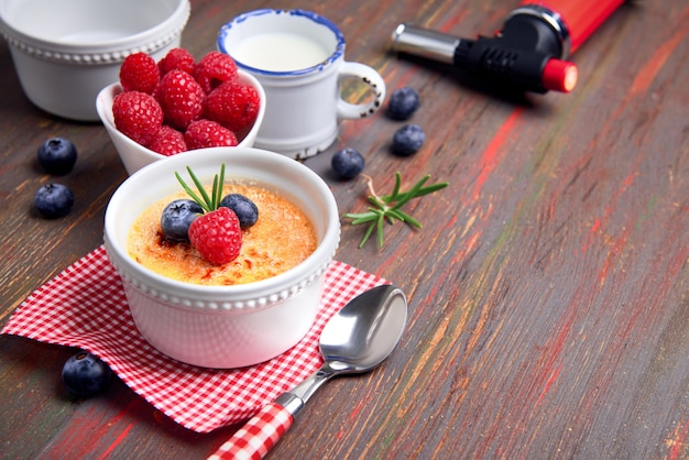 Creme brulee with raspberry blueberry and rosemary with ingredients