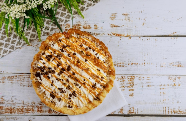 Creme pie with caramel chocolate topping on white wooden table
