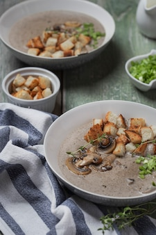 Creme soup with mushrooms and croutons in white bowl