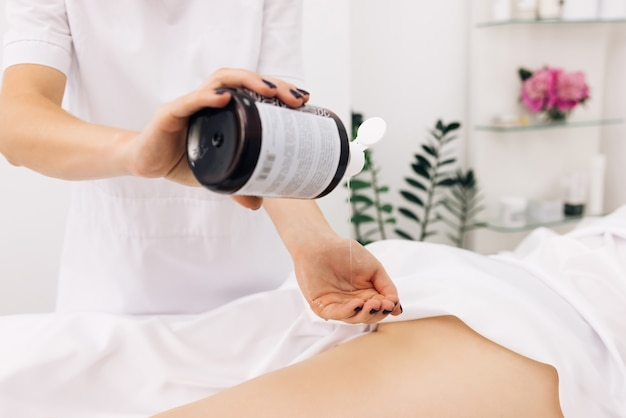 Creme treatment on woman legs with hydrating lotion preventing dry skin on female body parts closeup