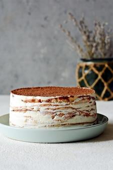 Блинный торт из тонкого блинчика со сливочным кремом, какао, шоколадом, сублимированной клубникой.