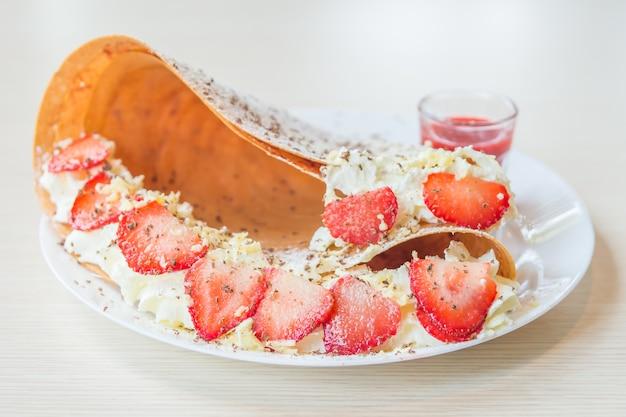 딸기 과일과 휘핑 크림을 곁들인 크레페 디저트