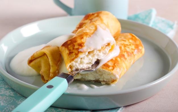 Блинчик с начинкой из мягкого сыра на тарелке