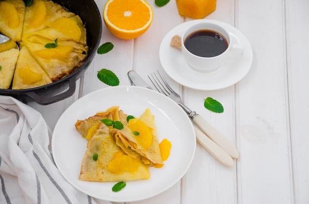 Креп сюзетт с апельсиновым соусом и чашка кофе на белом фоне деревянные.