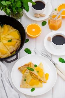 Креп сюзетт с апельсиновым соусом и чашкой кофе. вкусный и ароматный завтрак.