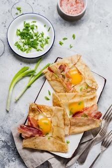 ライトグレーのコンクリートの表面に目玉焼き、チーズ、ベーコン、ネギの朝食用クレープ