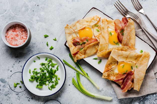 Crepe with fried egg, cheese, bacon and green onions for breakfast on a light gray concrete surface