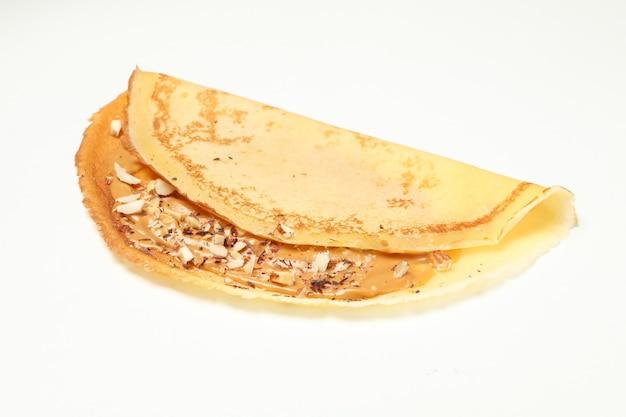 白い背景で隔離のピーナッツバターとナッツのクレープ