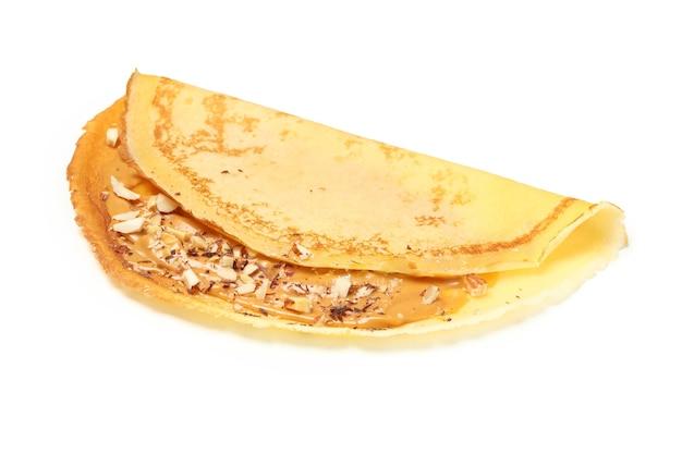 白い表面に分離されたピーナッツバターとナッツのクレープ