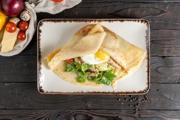 サラダと卵のクレープ。目玉焼き、鶏肉の切り身、野菜、サラダを添えたパンケーキの朝食またはランチのホットメインコース