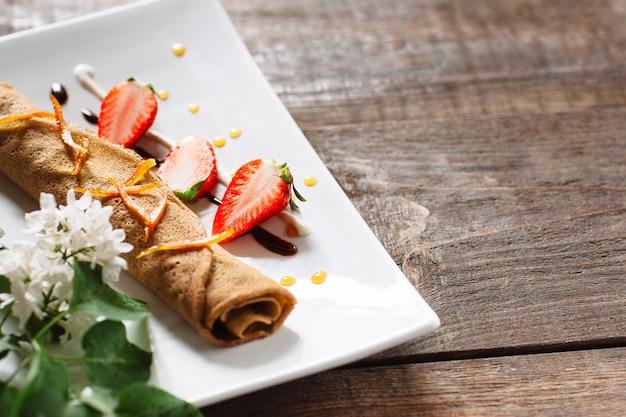흰색 접시에 딸기와 크레페