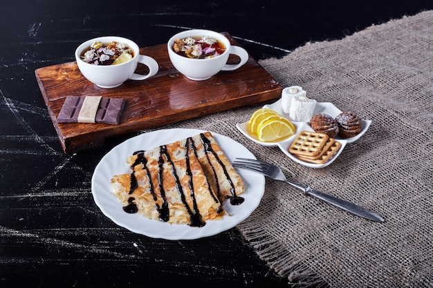 Блинчики в белой тарелке с шоколадным сиропом и чаем.