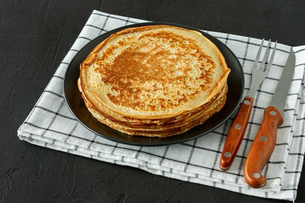 素朴なスタイルの木製の背景にクレープまたはロシアのブリニ。朝食やデザートに自家製の薄いクレープ。