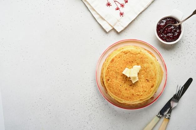 クレープや薄いパンケーキは、美しいセラミックプレートにバターとラズベリージャムを重ねます