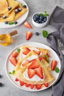 크레페 또는 크림 치즈, 신선한 딸기와 회색 콘크리트 배경에 흰색 접시에 꿀 얇은 팬케이크. 공간을 복사하십시오.