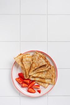 美しい白いセラミックプレートにクリームチーズと新鮮なイチゴのクレープパンケーキ。テキストまたはレシピ用のスペース。上面図。