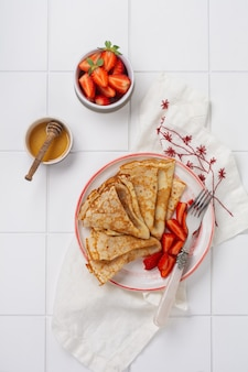 Crepes pancakes with cream cheese, fresh strawberry and honey for breakfast in beautiful white ceramic plate. space for text or recipe. top view.