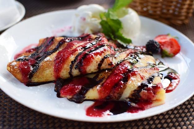 Блинчики с начинкой из фруктов и шоколадно-ягодными сиропами. подается с шариками мороженого и клубникой. тонкие блины, блины. сладкий десерт.