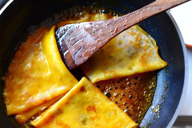 Crepes suzette in a pan with wooden spatula