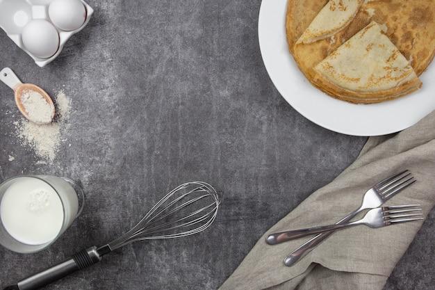 クレープ、小麦粉、卵、牛乳を調理するための材料が入った白い皿の上の薄いパンケーキ。