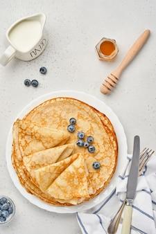 クレープ、薄いパンケーキ、または白いプレートにベリーを添えたブリニ